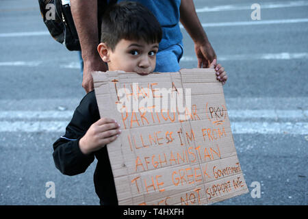Athens, Greece. 16th Apr, 2019. A child holds a placard at a demonstration against the Greek government's decision to demand refugees leave the apartments in which they have been living for newcomers in Athens, Greece, on April 16, 2019. Credit: Marios Lolos/Xinhua/Alamy Live News - Stock Photo