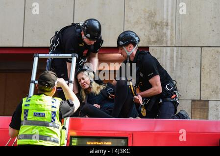 London, UK. 17th Apr, 2019. Police officers place a protester who glued herself to the roof of a DLR train carriage into a safety harness at Canary Wharf station in London, UK on April 17, 2019. This is part of on going climate change protests in London. Credit: Claire Dohert/Alamy Live News - Stock Photo