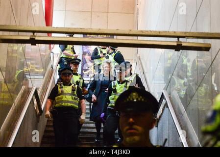 London, UK. 17th Apr, 2019. A climate change protester who glued herself to the roof of a DLR train at Canary Wharf DLR station is led away by the police. Credit: Claire Doherty/Alamy Live News - Stock Photo