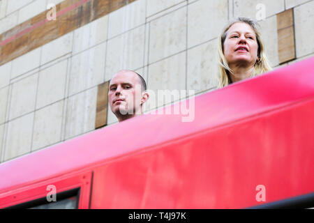 Two environmental activists are seen on the roof of a Docklands Light Railway train at Canary Wharf station during the third day of the Extinction Rebellion Climate Change protest.  The group is demanding decisive action from the UK Government on the environmental crisis. - Stock Photo