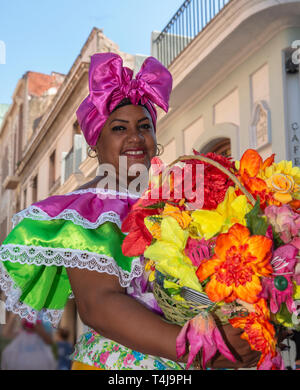 Cuban woman with traditional floral  clothing posing for tourists in street in  Old Havana, Cuba - Stock Photo