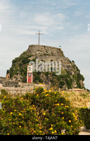 Historic bell tower inside the Old Fortress of Corfu Town in front of massive mountain with viewpoint over the whole city (Corfu Town, Corfu, Greece) - Stock Photo