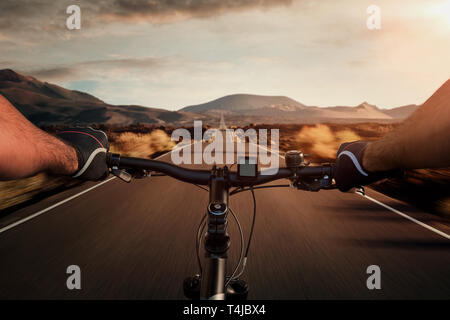 Riding a bicycle on an empty road through the volcanic landscape with copy space - Stock Photo