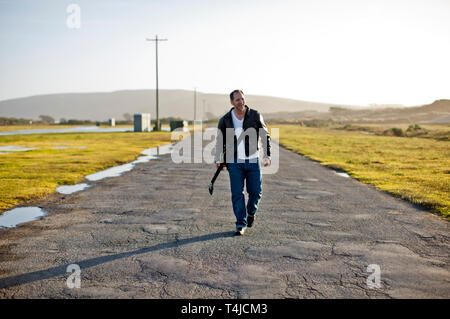 Smiling mid-adult man walking along a rural country road with his guitar. - Stock Photo
