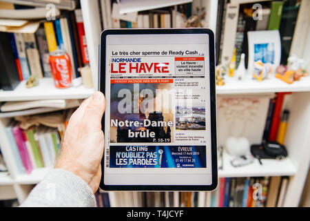 Paris, France - Apr 15, 2019: Man reading on iPad Pro Apple News Plus digital newspaper featuring on cover Notre-Dame Cathedral on fire causing damages Le Havre - Stock Photo
