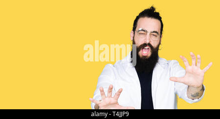 Doctor therapist man with long hair and bear wearing white coat afraid and terrified with fear expression stop gesture with hands, shouting in shock.  - Stock Photo