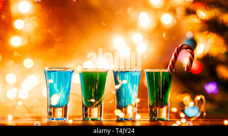 Christmas image of four wine glasses with green cocktail, caramel sticks - Stock Photo