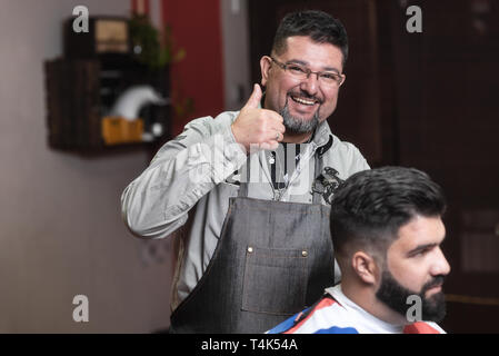 Happy barber customer satisfied with the result. Barber smiling showing thumb up . - Stock Photo