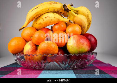 Natural fresh bio selected fruit in a glass bowl on a kitchen counter close to the window - Stock Photo