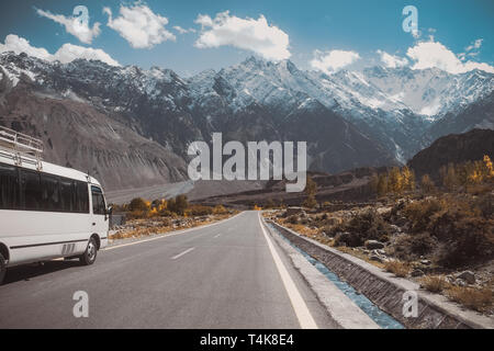 Paved road in Passu with a view of snow capped mountain range, Karakoram highway in Gojal Hunza. Gilgit Baltistan, Pakistan. - Stock Photo