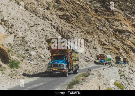 Gilgit Baltistan, Pakistan. October 11, 2015 : Pakistani decorated trucks travelling on paved road, transport goods via Karakoram highway along the mo - Stock Photo