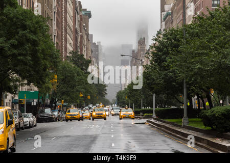 Head on view of multiple yellow cabs or taxicabs on Park Avenue in Upper East Side New York city, America, in the morning of an overcast and rainy day - Stock Photo