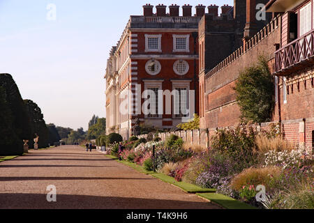 Georgian Facade of Hampton Court Palace and huge variety of colourful flowers and plants in the borders surrounding the building - Stock Photo