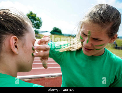 Girl Putting Green Face Paint On Friend For House Athletics