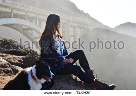 adult black and white border collie beside the woman sitting on the stone - Stock Photo