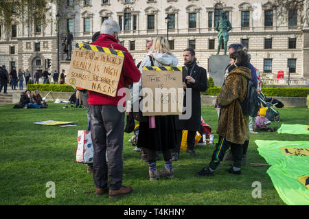 Demonstrators with banners congregate on Parliament Green, Westminster for the Extinction Rebellion demonstration - Stock Photo