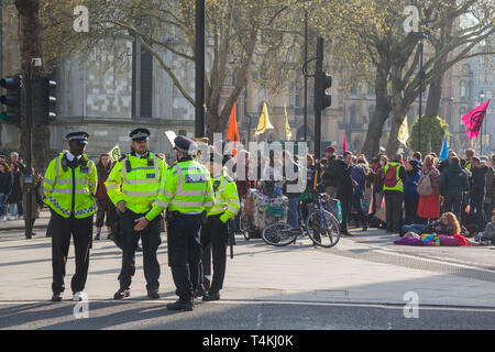 Metropolitan Police stand by on Parliament Square, Westminster for the Extinction Rebellion demonstration with protestors and banners behind - Stock Photo