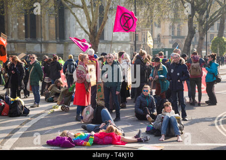 Demonstrators sit in the road blocking Victoria Street by Parliament Square, Westminster for the Extinction Rebellion demonstration - Stock Photo