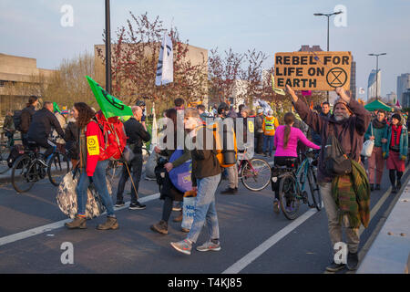 A protestor marches across Waterloo Bridge for the Extinction Rebellion demonstration with a placard 'Rebel for Life on Earth' - Stock Photo