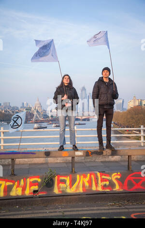 Two protestors stand holding flags on Waterloo Bridge for the Extinction Rebellion demonstration with the City of london behind - Stock Photo