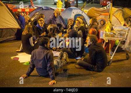 A group of students sit on the road at night at Marble Arch for the Extinction Rebellion demonstration