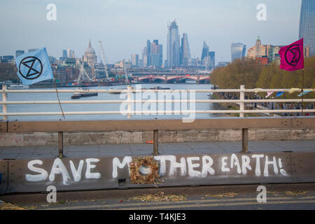 A 'Save Mother Earth' banner painted on Waterloo Bridge for the Extinction Rebellion demonstration with hte City of london behind - Stock Photo