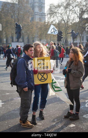 A young couple with a 'Save our Children' banner by Parliament Square, Westminster for the Extinction Rebellion demonstration - Stock Photo