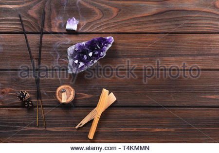 Composition of esoteric objects used for healing, meditation, relaxation and purifying. Amethyst stones, palo santo wood, Aromatic sticks on dark back - Stock Photo