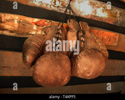 Boxing gloves on the wall. Old, vintage pair of leather mittens hangs on the wood wall. Red colors and soft lights. Gloves of retired boxer - Stock Photo