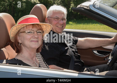 Smiling happy senior couple in a luxury convertible car - Stock Photo
