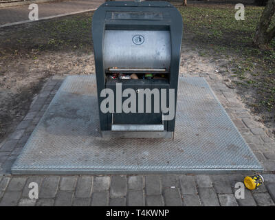 full city trash garbage container with coffee cup on the ground - Stock Photo
