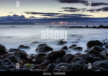 Seascape coastline of west Tenerife at dawn made using long exposure photography with nuetral density filters to create silky water and movement in th - Stock Photo