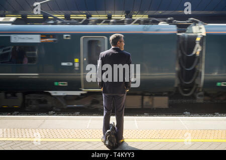 A commuter with a briefcase waits on the platform at Reading Station, Berkshire - Stock Photo