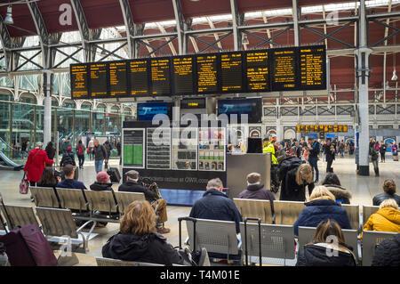 Travellers waiting by the illuminated display board at Paddington Station, london - Stock Photo