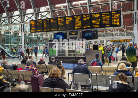 Travellers waiting by the illuminated display board at Paddington Station, london - Stock Photo