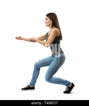 Side view of young woman in sleeveless gray top and blue jeans doing kata with long step right forward isolated on white background. - Stock Photo