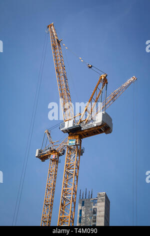 Two large Liebherr construction cranes against a clear blue sky - Stock Photo
