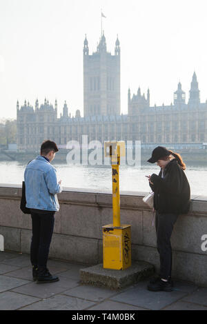 Two young foreign tourists look across to the Houses of Parliament over the River Thames - Stock Photo