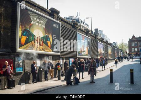 Smokers using the exterior smoking area outside Paddington Station, London - Stock Photo
