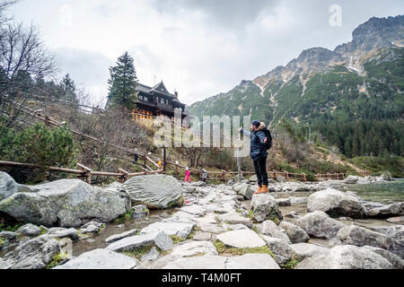 Hiker pointing to the wooden shelter in Tatra mountains - Stock Photo