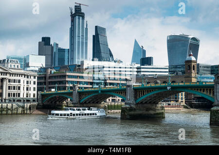 The tourist sightseeing boat Mercia passing under Southwark Bridge on the River Thames with the iconic high rise buildings in the background. - Stock Photo