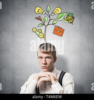 Serious student with arms touching his chin - Stock Photo