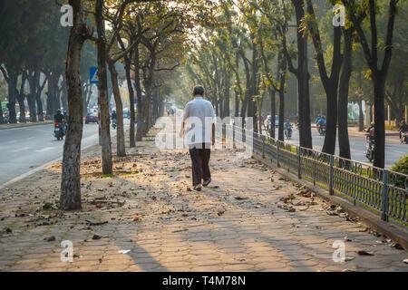 An elderly man is walking through sidewalk among trees in the early morning on Hanoi street - Stock Photo