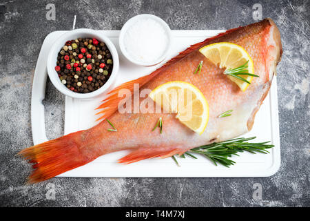 Fish raw snapper with lemon slices, herbs rosemary, salt and pepper on dark background. Healthy food and dieting concept. Top view - Stock Photo