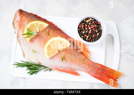 Fish raw snapper with lemon slices, herbs rosemary, salt and pepper on white background. Healthy food and dieting concept. Top view - Stock Photo