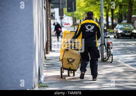 Postbote in der Großstadt zu Fuss unterwegs.