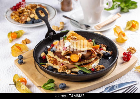 Delicious sweet American pancakes served on a fry pan with fresh fruits, nuts and chocolate sauce - Stock Photo