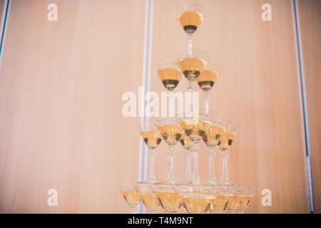 Champagne glasses standing in a tower at the party. - Stock Photo