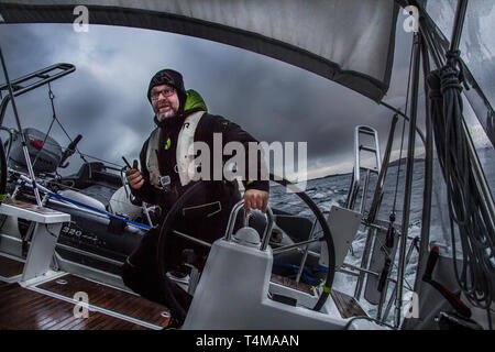 A skipper at the helm of a sailing yacht in the middle of a storm, Arctic Circle, Norway. - Stock Photo