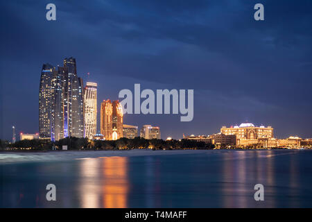 ABU DHABI, UNITED ARAB EMIRATES - April 5, 2019: Etihad Towers (left), which consist of residential apartments and a Jumeirah hotel, and Emirates Pala - Stock Photo